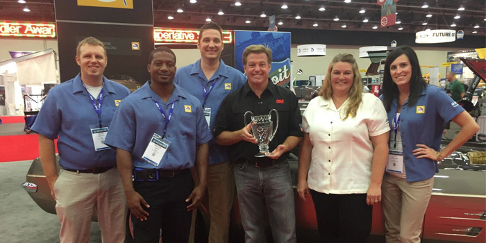 Members of the BASF Automotive Refinish team accepting the Top Custom Car Award with Chip Foose. From left to right: Justin Griffin, BASF sales development intern; Marcus Grant, BASF sales development intern; Steve Shemanski, BASF customer care representative; Chip Foose; Tina Nelles, BASF marketing services manager and Kate Kalahar, BASF customer care representative.