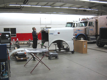 A technician at Peterbilt of Northwest Ohio repairs a semi-truck hood assembly.
