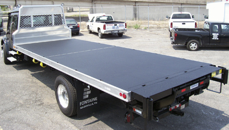 The application of bedliner material is seen here on the deck of a rollback recovery truck. (Photo courtesy of Langeman Manufacturing, LTD.)