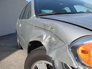 photo 6: side angle of a damaged fender to show the dent's severity. the building behind the car provides a dark, simple background.