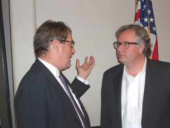 Attorney John Eaves Jr. (right) speaks with an attendee at the meeting.