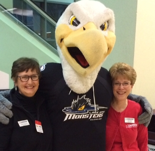 Kerry Ott and Cheryl Cameron, marketing managers for Cleveland CARSTAR stores, pose with Lake Erie Monsters mascot Sully.